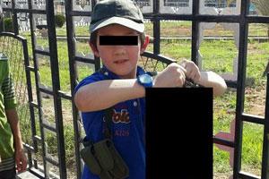7岁男童提士兵头颅合影 其父为之骄傲